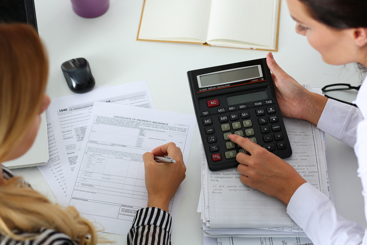accountant-holding-calculator-while-helping-client-fill-out-paper-financial-forms-at-table