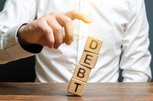 business tax debt concept, man pushing over a debt tower