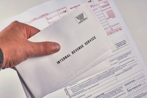 Human holds in hand three mails from the Internal Revenue Service next to w-9, 1099-misc and 1099-k tax forms