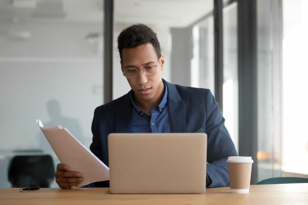Man looking at finances on laptop and filing his taxes