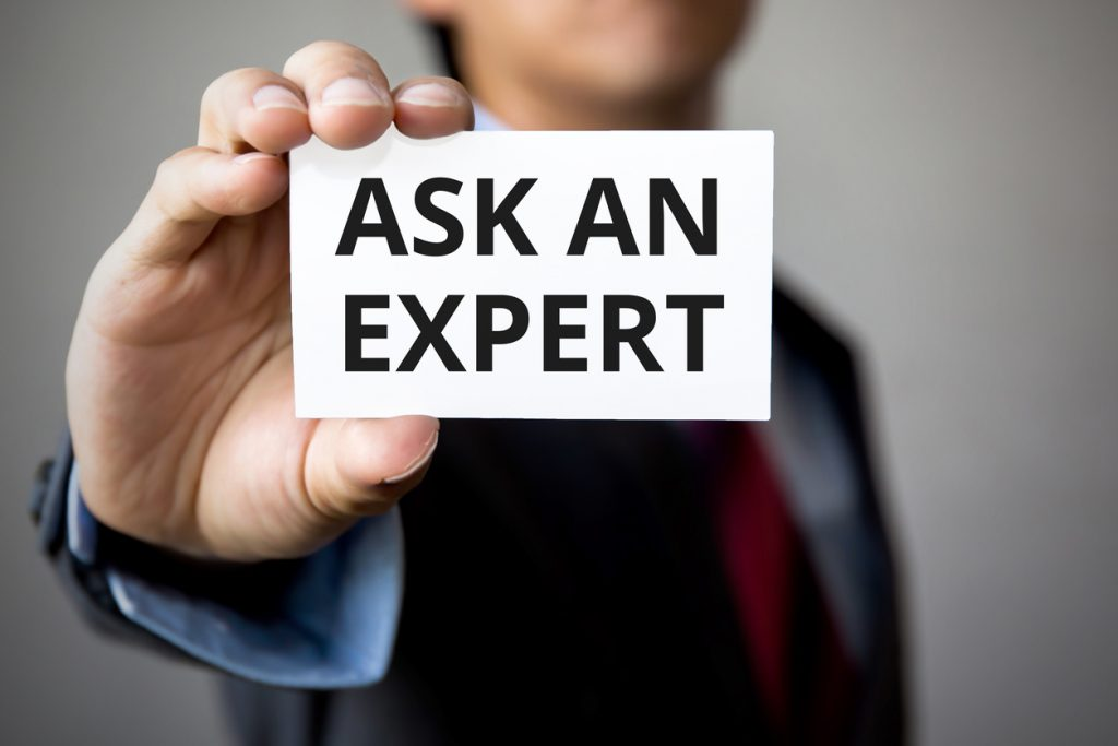 "Man holding a card with the words ""ask an expert"" on it, help with employee benefit IRS forms concept"