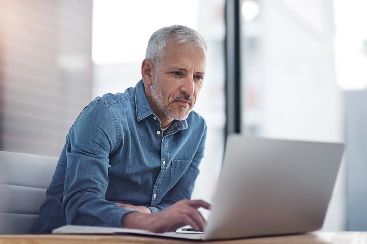 Older business owner on laptop looking at IRS business forms