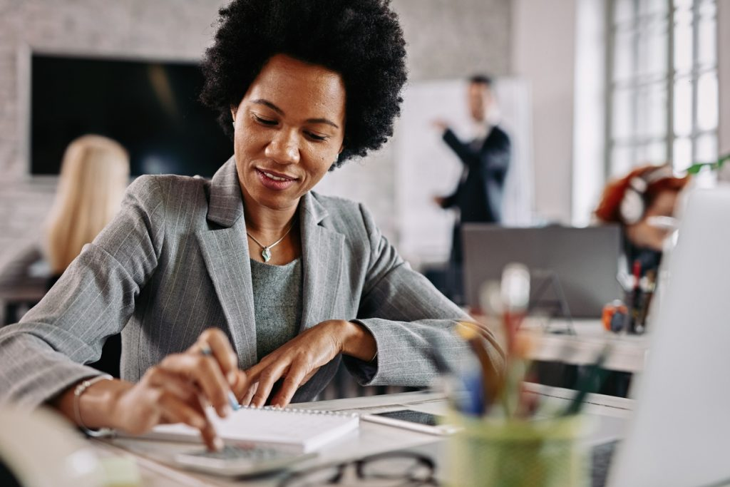 Business woman doing calculations at her desk, IRS business forms concept