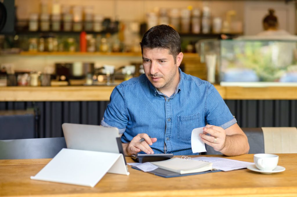 Small business owner filling out taxes and paperwork, small business tax forms concept