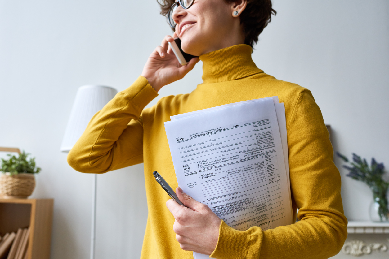Young woman talking on the phone and holding multiple IRS forms