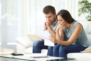 Pensive spouses managing family budget during a financial hardship.