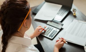 woman performing double-entry bookkeeping