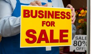 business owner putting up a sign selling your small business