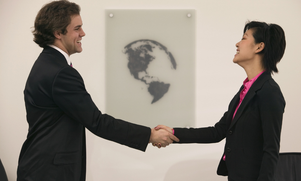 two parties closing international business deal who may need a foreign bank account