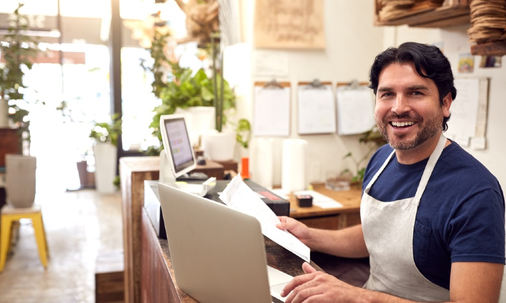 small business owner wearing an apron works on a laptop to determine if business grants are taxable income