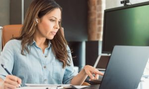 woman sitting at a desk getting virtual tax preparation services