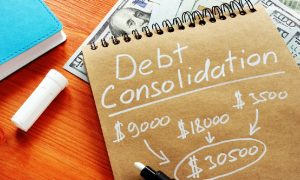 A notebook with some business debt consolidation calculations sits atop some cash.