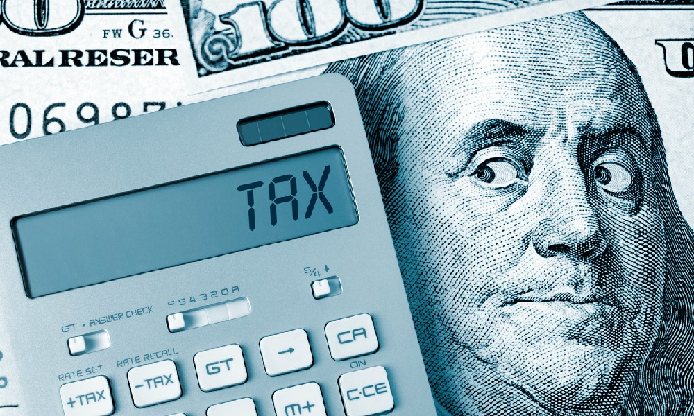 An illustration of Benjamin Franklin on a $100 bill looking at a tax calculator symbolizes issues that come up when you don't pay state taxes.