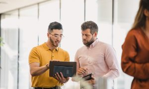 A business owner meets with a business operations consultant while both look at a tablet.