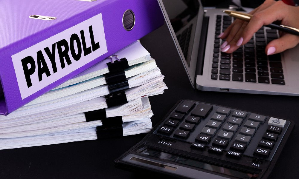 A payroll binder sits atop a stack of paperwork as a person uses a calculator to offer payroll services for small businesses.