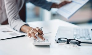 A taxpayer uses a calculator to figure out what to do with the 1099-K tax form.