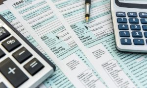Tax forms sit on a table with pen and calculators as someone prepares to fill out form 8965.
