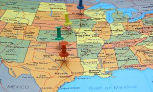 Four pins showing on a colorful map of the United States illustrate someone needing to pay multiple state tax returns.