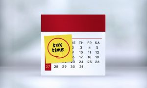 """open tax year tax calendar with a sticky note saying """"tax time."""""""