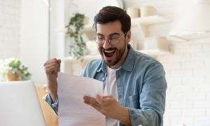 man looks excitedly at his tax return because he lowered his taxes by understanding a tax credit vs. deduction