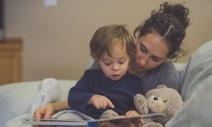 mother reads a book in bed to her son, who she's claiming as a dependent.