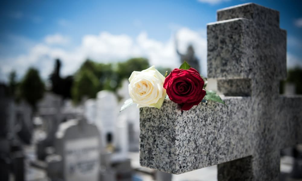 A red and white rose on top of a tombstone raises the question: Are funeral expenses tax-deductible?