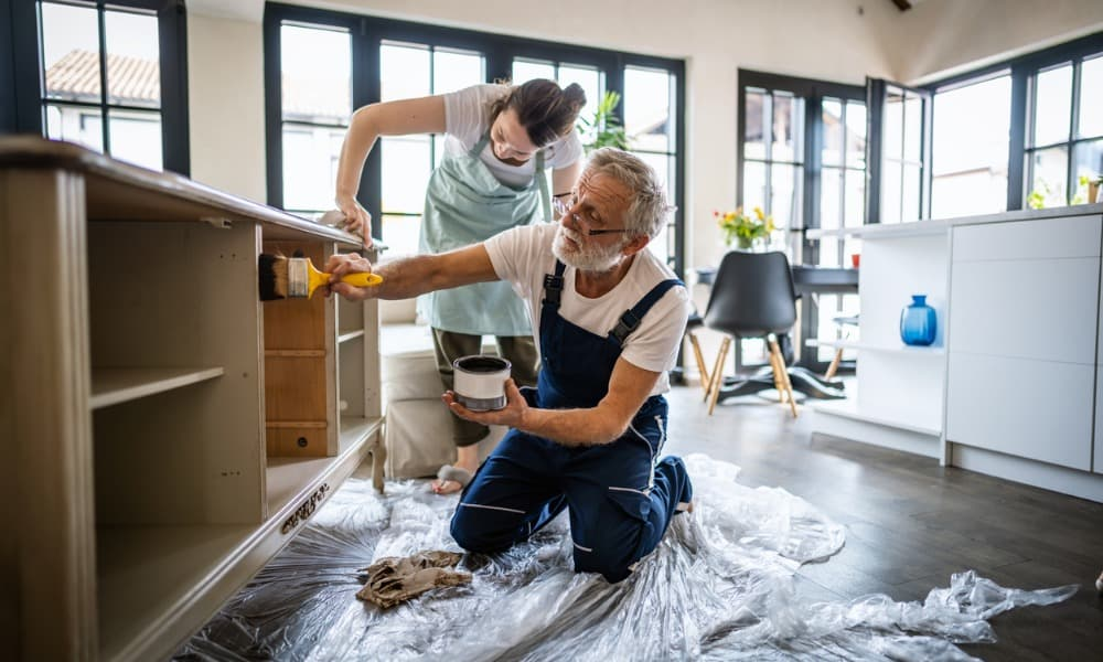 man and woman painting cabinets and wondering if they can write off home improvements.