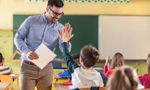 A teacher high-fiving a student in class is likely eligible for tax deductions on his educator expenses.