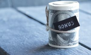 """A roll of cash with a """"bonus"""" label signifies a bonus waiting to be taxed."""