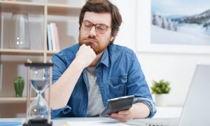 A man with a calculator trying to figure out what to do after he filed taxes late