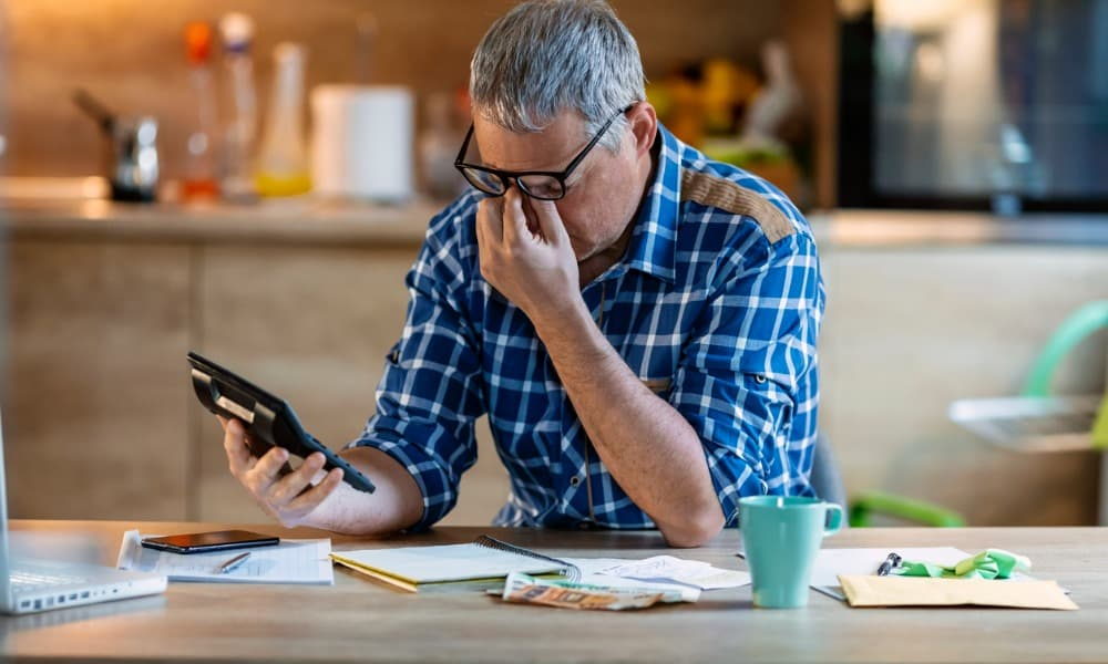 A man with a calculator and tax forms is frustrated that he still owes taxes.