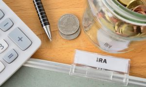 An IRA folder sits next to a calculator, a pen, and some change, signifying this guide to IRS Form 5498.